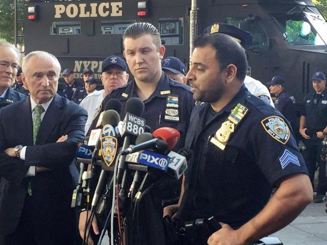 In this photo provided by the New York Police Department (NYPD), Sgt. Hameed Armani, right, and Officer Peter Cybulski talk at a news conference, Thursday, July 21, 2016 at Columbus Circle in New York, about the hoax bomb that was tossed into their police van the night before in Times Square.