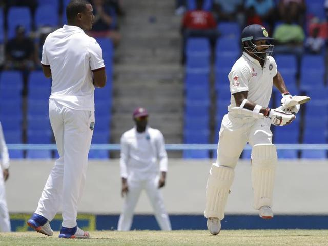 West Indies captain Jason Holder, left, hand the ball to Shannon Gabriel during the first inning of day one of their first Test against India at the Sir Vivian Richards Stadium in North Sound, Antigua, on Thursday.