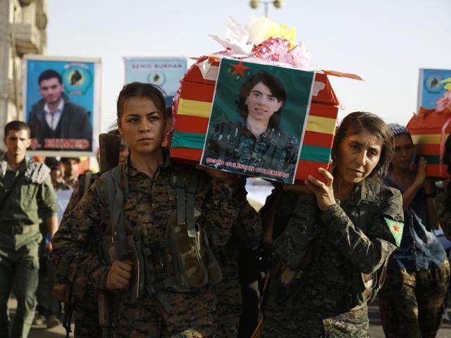 Syrian-Kurdish women carry the coffin of a female fighter in Syria's northeastern city of Qamishli on Thursday during the funeral of sixteen fighters killed battling the Islamic State (IS) group in Manbij.