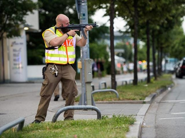 A policeman secures the area around a shopping mall in Munich on July 22, 2016 following a shooting earlier. At least eight persons have been killed and several wounded in a shooting at a shopping centre in Munich on Friday, German police said.  (AFP)