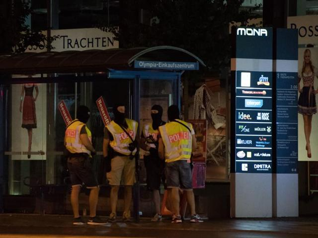 Masked police stand at a bus stop in front of the Olympia mall where a shooting took place in Munich on Friday.