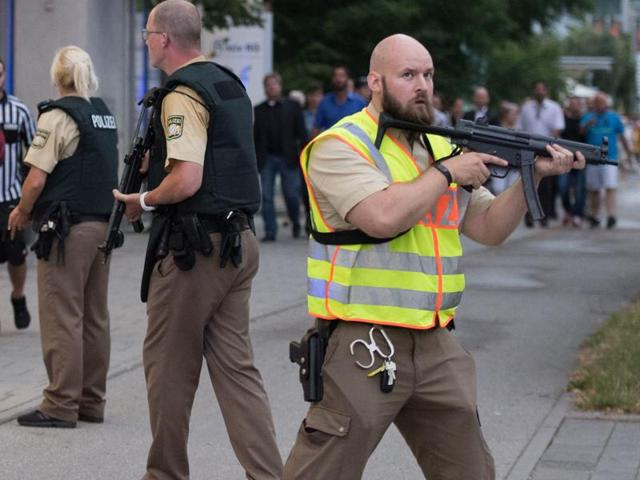 Police escort people who leave the Olympia mall in Munich, southern Germany, on Friday after shots were fired.