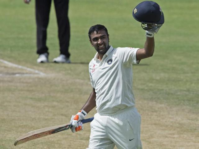 Ravichandran Ashwin raises his bat and helmet after scoring a century against West Indies during day two of their first cricket Test match at the Sir Vivian Richards Stadium in North Sound, Antigua on Friday
