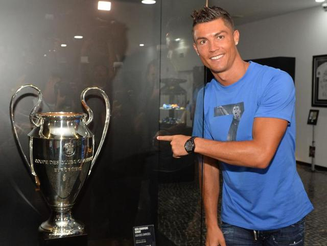 Portugese forward Cristiano Ronaldo points a UEFA Champions league cup.