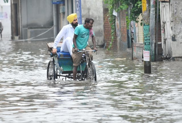 A rickshaw puller wades through a water-logged lane in Jalandhar, passenger in tow.
