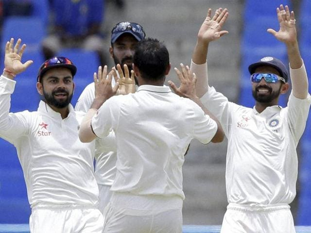 India cricketer Mohammed Shami (C) is congratulated by teammates during day two against West Indies.