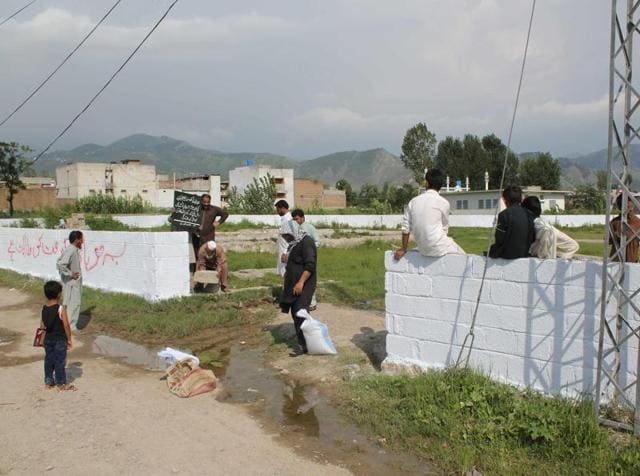 Pakistani workers mark the edges of the patch of ground where the house where al Qaeda leader Osama Bin Laden was killed once stood in Abbottabad on July 23, 2016. The military has erected a wall around the 3,800 square feet plot.