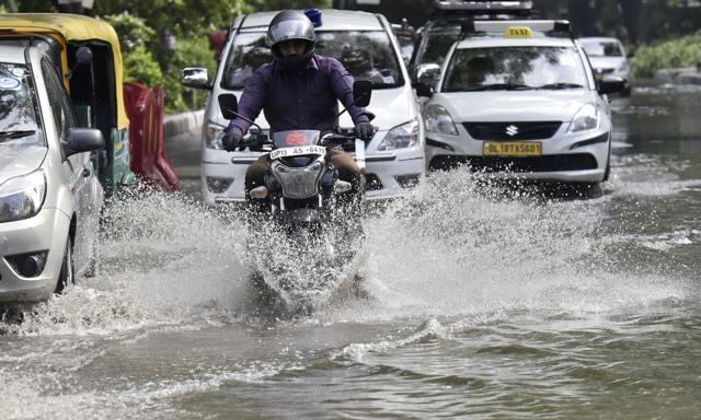 Vehicles wade through logged rain water during a heavy rainfall at South Delhi Mehrauli, airport road.