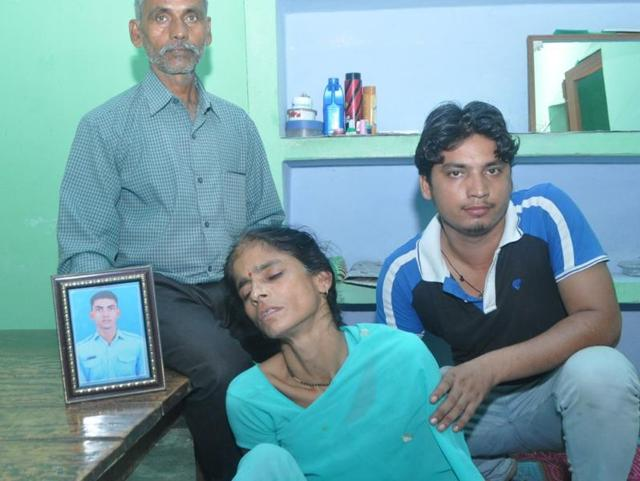 Family members with a photo of one of the missing IAF personnel.