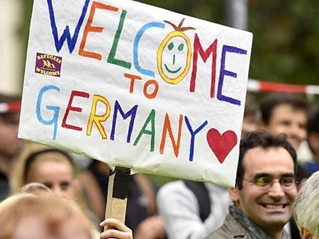 People welcome refugees with a banner reading 'welcome to Germany' in Dortmund, Germany in Sept 2015, where thousands of migrants and refugees arrived by trains.