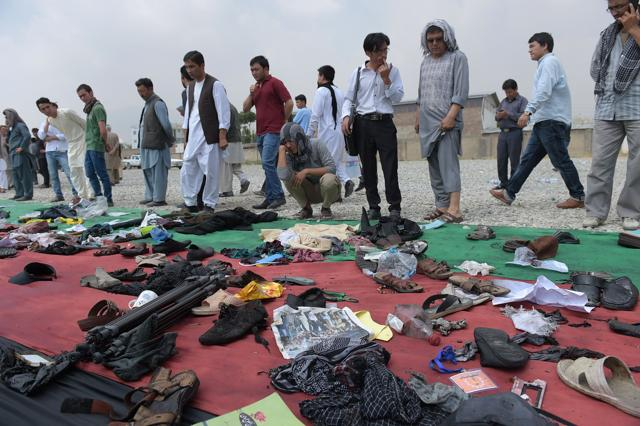 Relatives and friends inspect belongings of those who were killed in the twin suicide attack in Kabul.