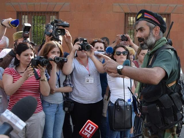 An armed man speaks to the press after pro-opposition gunmen locked in a week-long hostage standoff with Armenian authorities released the final four police officers held captive in Yerevan.