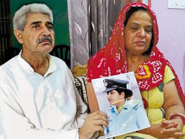 The parents of flight lieutenant Deepika Sheoran showing her picture at their house in Loharu, Bhiwani, on Saturday.