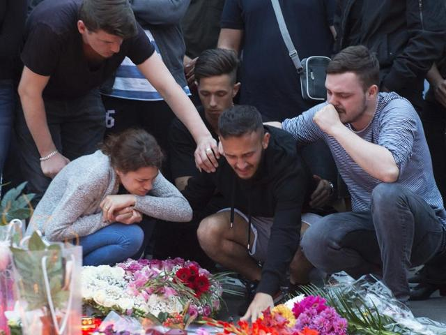 People mourn with flower tributes near the Olympia shopping centre where a shooting took place leaving nine people dead the day before in Munich, Germany.