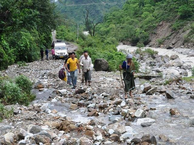 People walk across the debris after monsoon floodwaters devastated a village road in Chaomli district of Uttarakhand.(AFP)