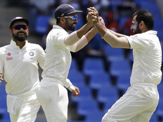 India's bowler Mohammed Shami, right, celebrates with teammates taking the wicket of Marlon Samuels.