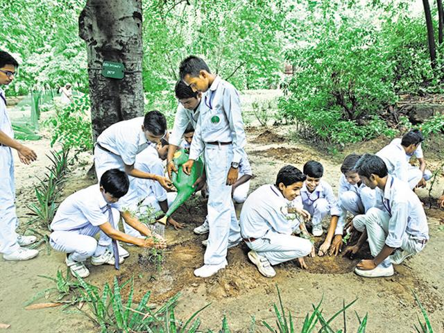 The students of NDMC schools during a plantation drive at Lodhi Garden in New Delhi .