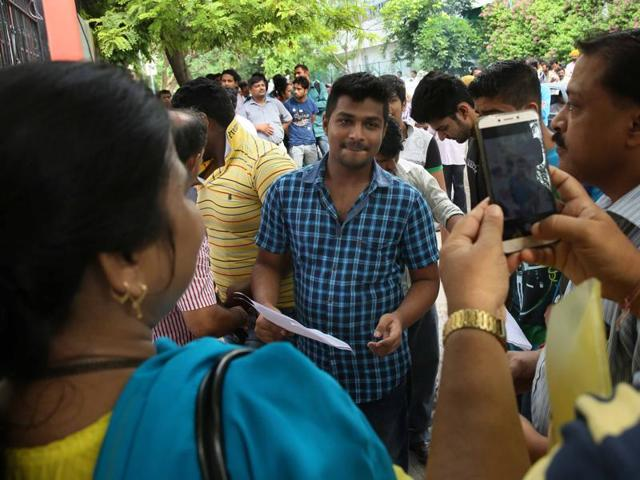 An aspirant of NEET-2 gets a photograph taken by his parents as he enters the examination center in Jaipur, Rajasthan on Sunday.