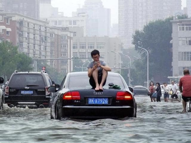 A man sits on top of a car as he is stranded on a flooded street in Tianjin, China.