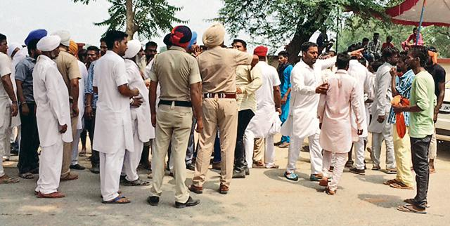 Cops trying to pacify Shiromani Akali Dal workers during a clash between two factions of the party at Surjit Nagar village near Bathinda on Sunday.