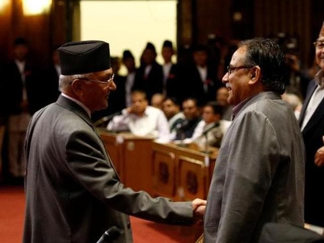 Nepal's Prime Minister KP Oli shakes hand with Unified Communist Party of Nepal (Maoist) chairman  Pushpa Kamal Dahal 'Prachanda', right, after announcing his resignation in Kathmandu.