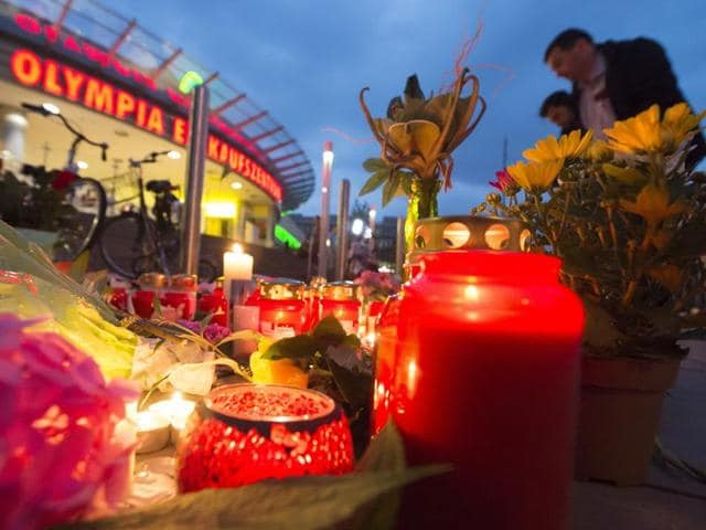 People gather to read tributes among the flowers and candles near to the Olympia shopping center where a shooting took place in Munich, Germany.