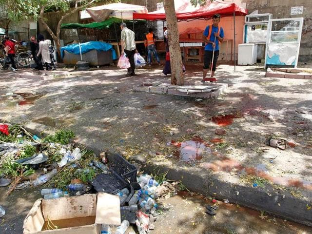 An Iraqi worker cleans the pavement at the site of a suicide bombing on Sunday near a checkpoint in the Kadhimiyah area, home to a major Shia shrine, in northern Baghdad. Another blast in Khales town of north Iraq took at least 14 lives on Monday.