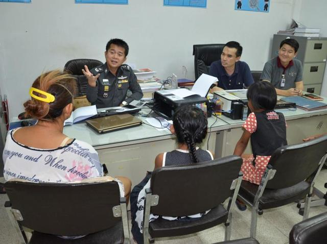 A policeman speaks to two eight-year-old girls after they tore voter lists off a wall because they liked the pink paper it was printed on, in Bangkok.
