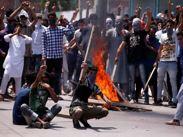 Protesters hold sticks as they shout slogans during a protest in Srinagar, in Kashmir.