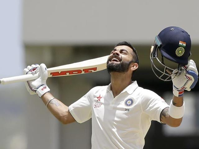 India skipper Virat Kohli kisses the pitch after scoring a double-century on day two of the first Test against West Indies.