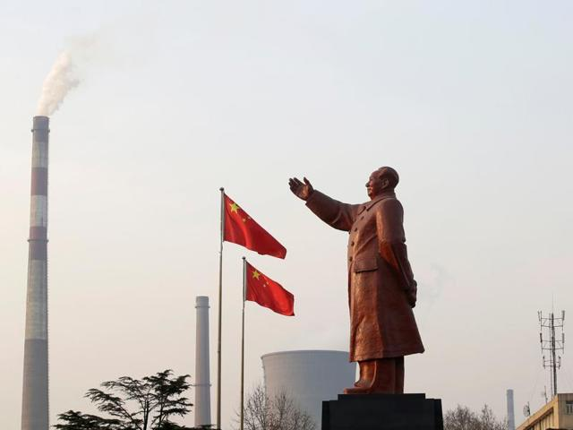 A statue of former Chinese leader Mao Zedong is seen in front of smoking chimneys in Wuhan, Hubei province. China's Communist Party controls Xinhua, the controversial news agency accused of espionage and propaganda.