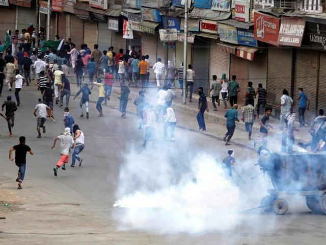 Smoke billows from a tear gas shell fired by police as demonstrators run for cover during a protest in Srinagar against recent deaths in Kashmir.