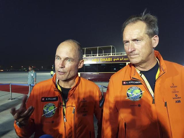 Pilots Andre Borschberg (L) and Bertrand Piccard celebrate after their arrival on Solar Impulse 2, a solar powered plane, at an airport in Abu Dhabi, United Arab Emirates July 26