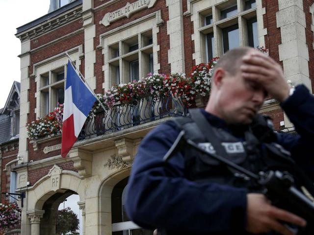A policeman reacts as he secures a position in front of the city hall after two assailants had taken five people hostage in the church at Saint-Etienne-du -Rouvray near Rouen in Normandy.