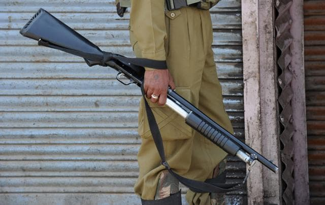 An Indian paramilitary trooper holds a pellet gun after clashes with Kashmiri protestors in Srinagar.