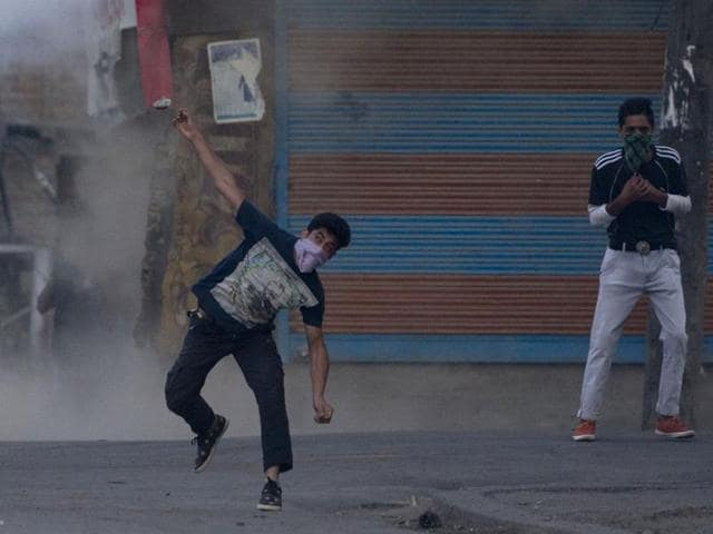 A masked Kashmiri protester throws a stone at  policemen during a protest in Srinagar, Kashmir.
