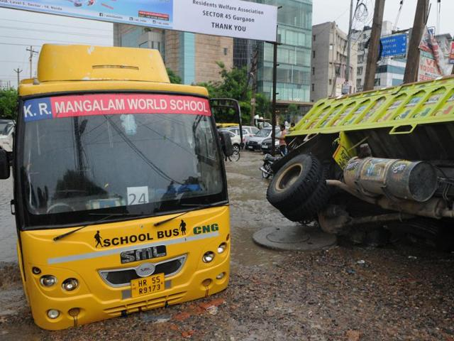 A school bus of KRMangalam World School and a truck loaded with construction material stuck in gravel after a road caved in at sector 45.