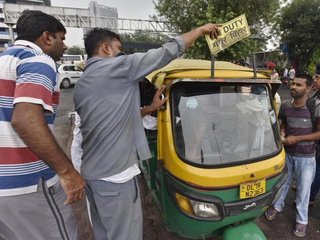 An auto driver removes the 'On Duty' sign during the indefinite strike called by Delhi's Auto and Taxi unions against app-based taxi services.