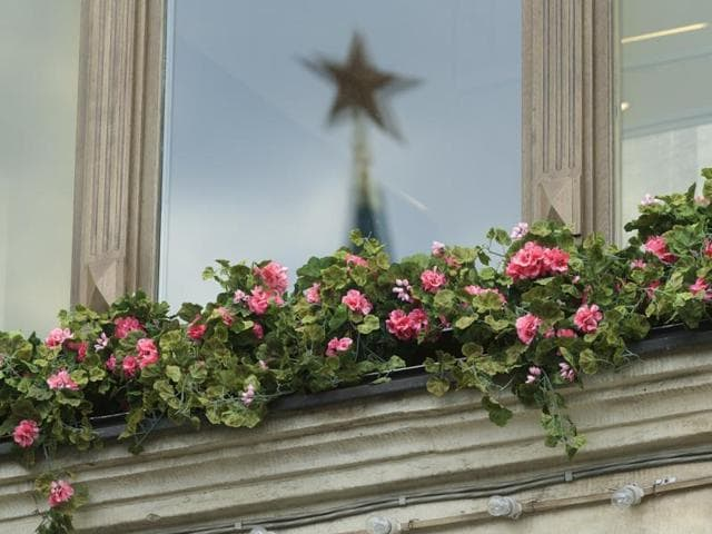 In this file photo, a ruby star on the Kremlin's Nikolskaya Tower is reflected in a window glass of a department store in Red Square in Moscow, Russia.