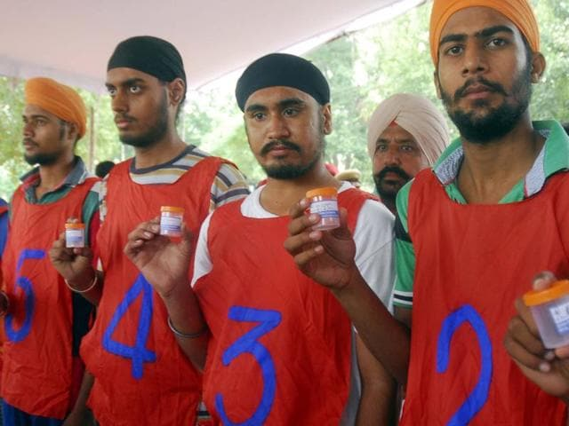 Candidates at the police recruitment rally hold urine samples for dope tests at Gandhi Ground in Amritsar on Wednesday.