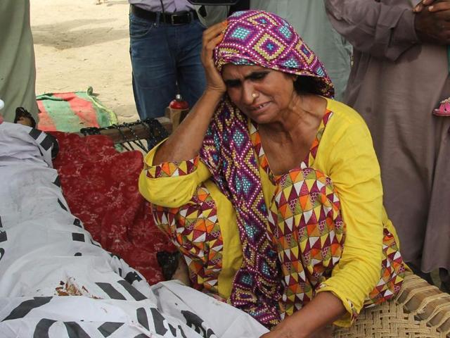 Qandeel Baloch's mother mourns alongside her body during her funeral in Shah Sadar Din village, around 130 kilometers from Multan.