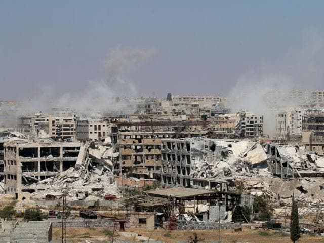 Smoke billows from buildings during an operation by Syrian government forces to retake control of the rebel-held district of Leramun on July 26, 2016. Two bombs hit the northern city of Qamishi, targeting the Kurdish administrative centre on July 27.