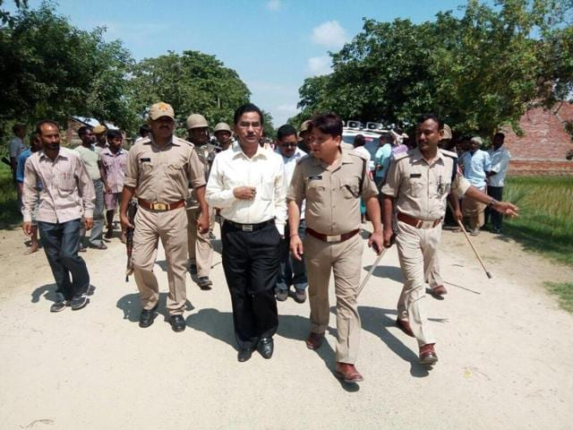 Police officials visit the village where a Dalit couple was hacked to death in Mainpuri district on Thursday.