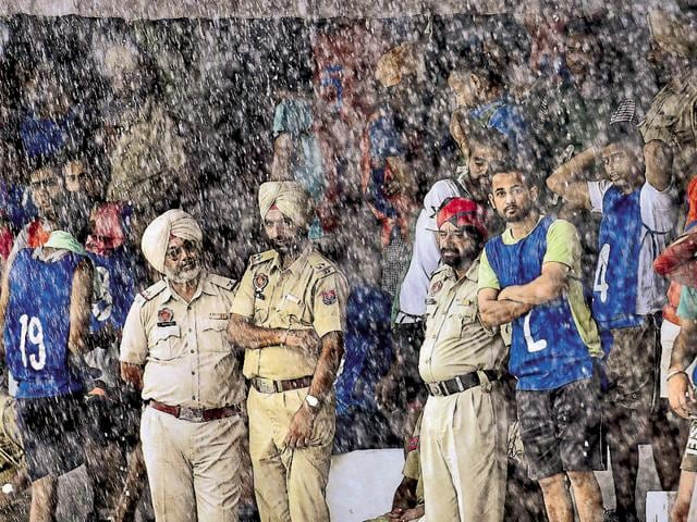 Cops waiting for the rain to stop in Amritsar on Wednesday.