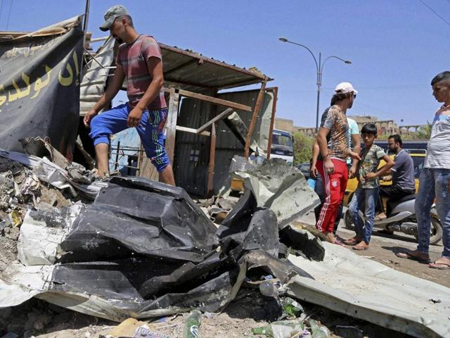 Civilians gather at the scene of a suicide bombing at the northern neighborhood of Shula, Baghdad, Iraq, on Wednesday.