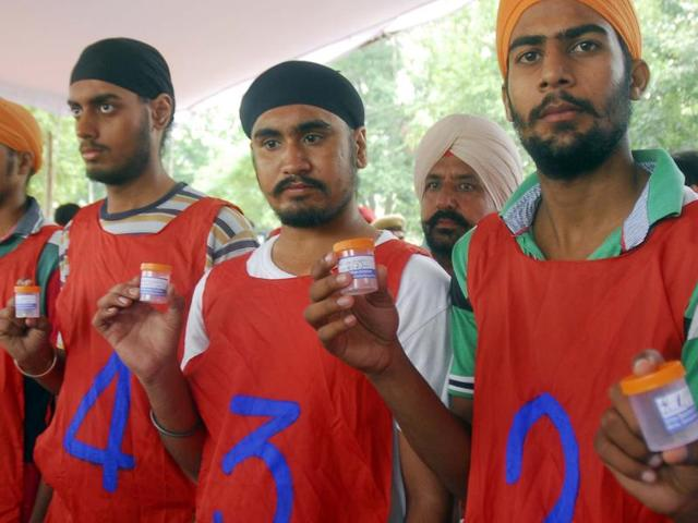 Aspirants submit samples for dope test at the police recruitment centre in Patiala on Wednesday.
