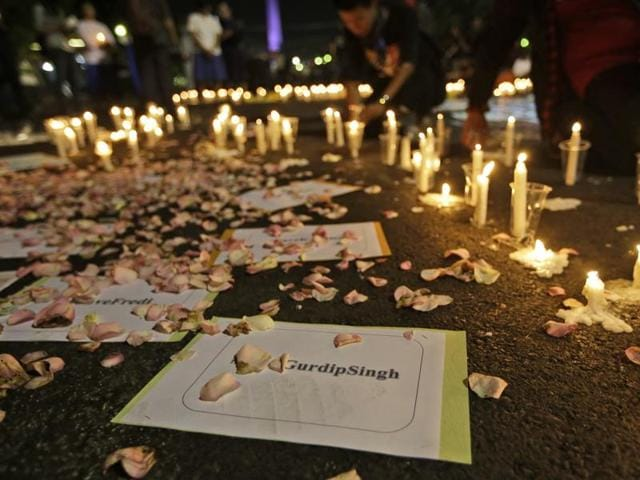 Activists light candles around posters with the names of death row inmates awaiting during a vigil against death penalty outside the presidential palace in Jakarta.