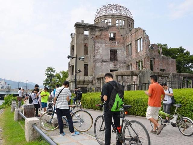 In this July 26, 2016 photo, people play Pokemon Go near the Atomic Bomb Dome at Hiroshima Peace Memorial Park in Hiroshima, Japan.