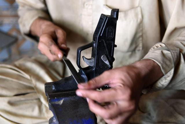 In this photograph taken on June 6, 2016, a Pakistani gunsmith makes a pistol at a small workshop in the tribal area of Darra Adamkhel, some 35 kilometres south of Peshawar.