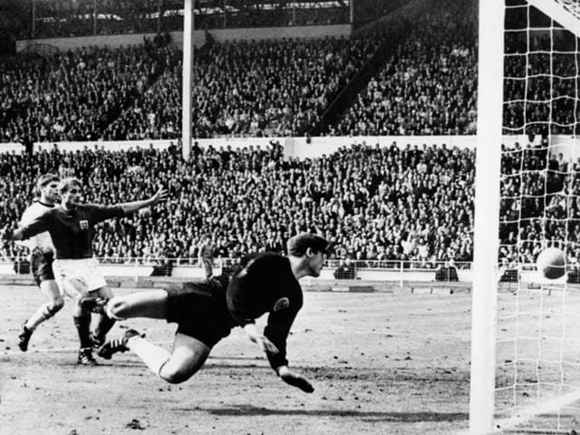 West Germany's goalkeeper Hans Tilkowski watches the ball bounce off the crossbar following a shot by English forward Geoff Hurst (not pictured) as English forward Roger Hunt (arms raised) and West Germany's defender Wolgang Weber look on during the overtime period of the World Cup final on July 30, 1966 at Wembley stadium in London.